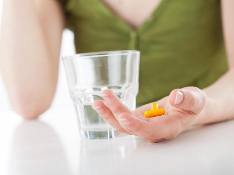 Bild zu Eine Frau mit Wasserglas und Tabletten