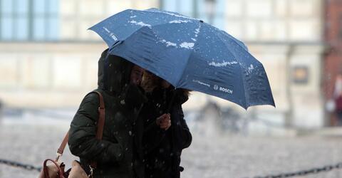 Passanten mit Regenschirm auf der Maximilianstraße in München während eines Regenschauers