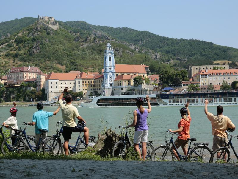 Bild zu Menschen mit Fahrrädern am Ufer