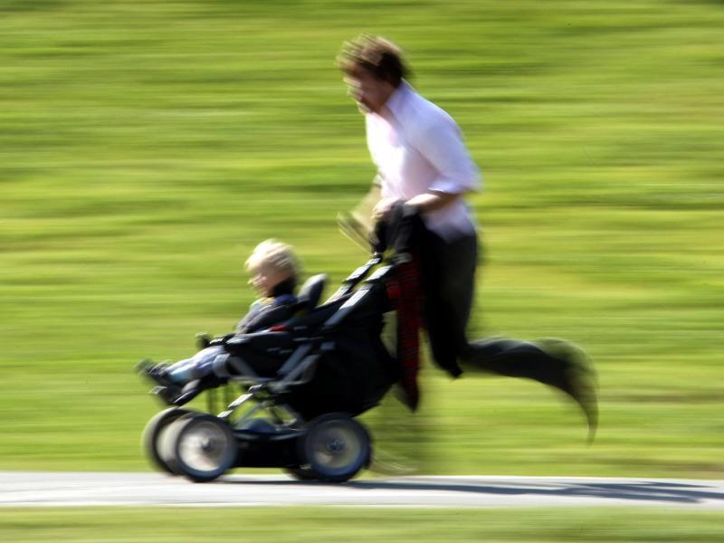 Bild zu Mann läuft mit Kinderwagen