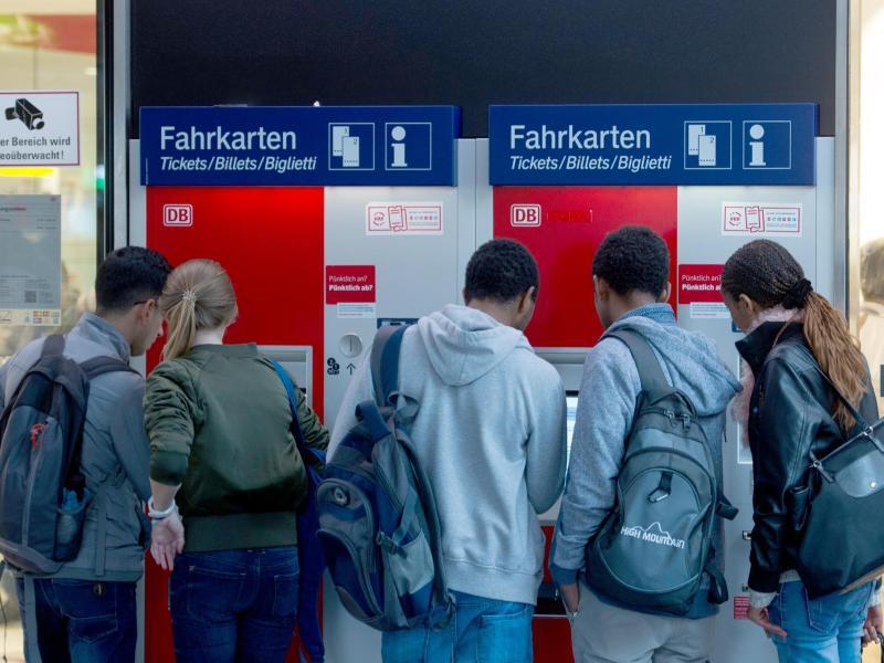 Bild zu Reisende stehen an einem Fahrkartenautomat