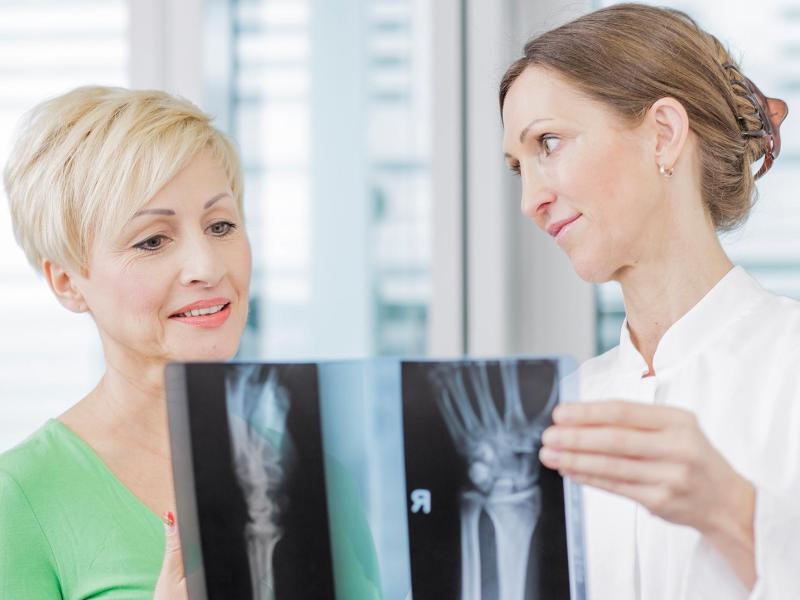 Bild zu Arzt mit Patientin und Röntgenbildern