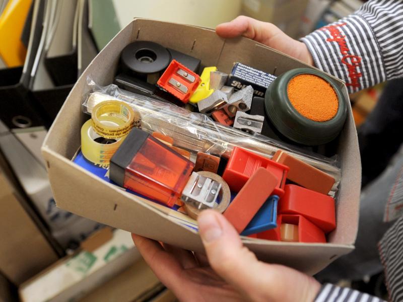 Bild zu Ein Mann zeigt Büromaterialien