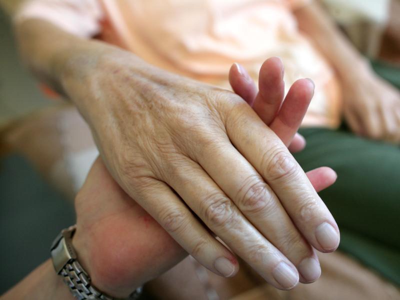 Bild zu Hand einer kranken Frau in der Hand einer Pflegerin