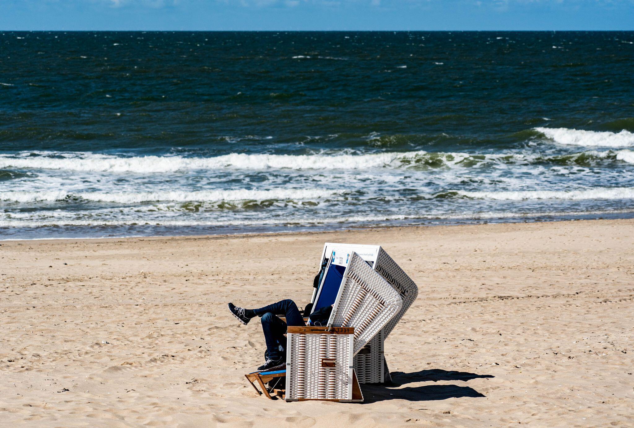 Bild zu Ein Mann sitzt in einem Strandkorb