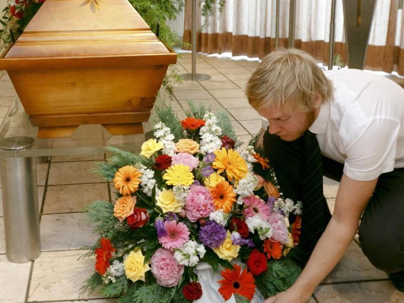 Bild zu Blumengesteck vor Grab