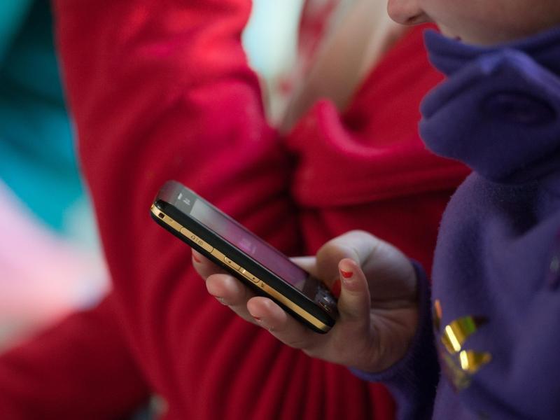 Bild zu Eine Schülerin mit einem Smartphone