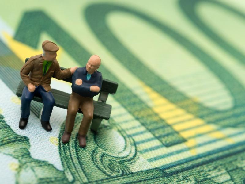 Bild zu Geldschein und Männer sitzen auf einer Bank