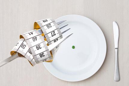 Maßband und Teller mit einer Erbse