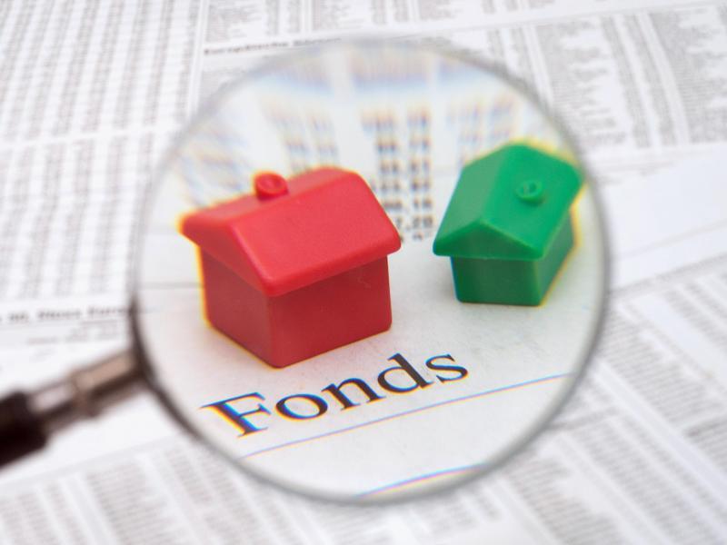Bild zu Lupe mit Kleinhäusern auf Fond-Papier