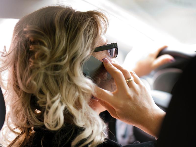 Bild zu Autofahrerin mit Handy am Ohr