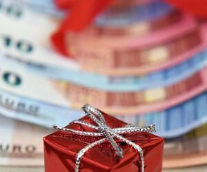 Ein Minigeschenk liegt auf Geldscheinen