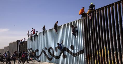 Mitglieder der Migrantenkarawane erreichen die Grenzmauer