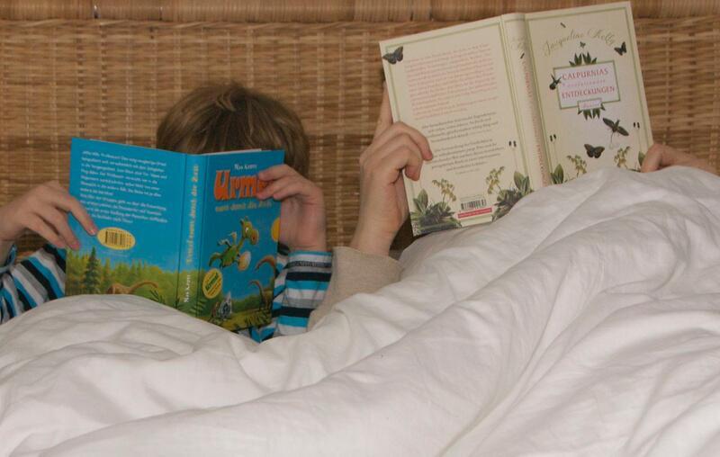 Bild zu Bloggerin ließt mit Sohn im Bett.